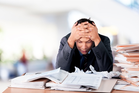 Photo pour Surprised young businessman with stack of papers - image libre de droit