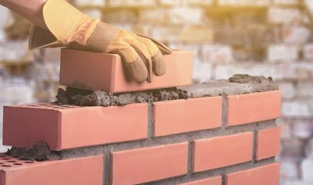 Photo pour Worker builds a brick wall in the house - image libre de droit