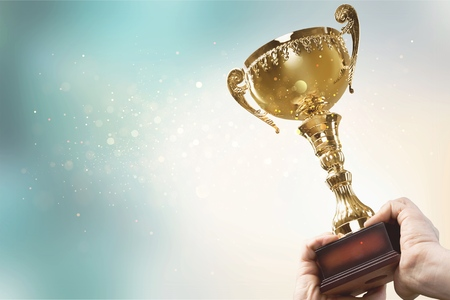 Foto de Hands holding golden trophy on a light background - Imagen libre de derechos