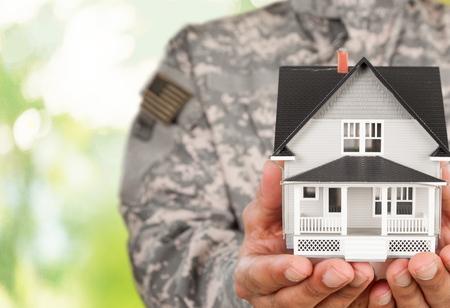 Photo pour Soldier Holding a Model of House - image libre de droit
