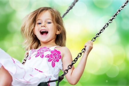 Photo pour Little child blond girl having fun on a swing - image libre de droit