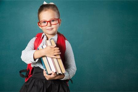Photo pour Cute little schoolgirl in glasses on blackboard - image libre de droit