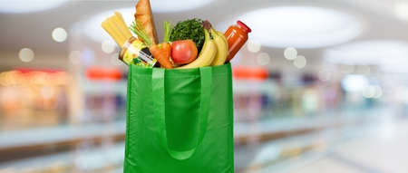 Photo for Eco friendly reusable shopping bag filled with vegetables on a blur background - Royalty Free Image