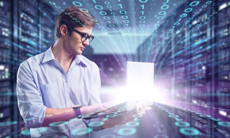 Foto de young it engeneer business man with thin modern aluminium laptop in network server room - Imagen libre de derechos