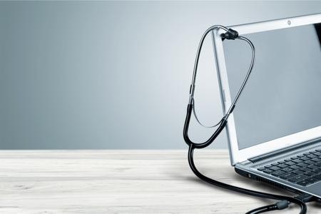 Photo pour Laptop diagnosis with  stethoscope on background - image libre de droit