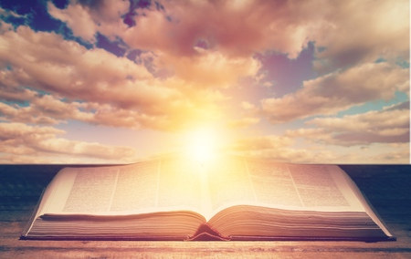 Foto de open bible on wooden table over the light through dark cloudy sunset sky. Christian concept show the word of God is the light of mandkind - Imagen libre de derechos