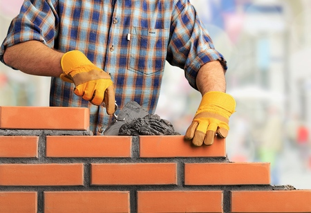 Photo pour Bricklayer industrial worker installing brick masonry - image libre de droit