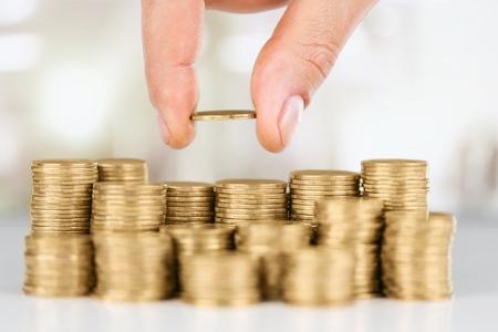 Photo pour Savings, close up of male hand stacking - image libre de droit