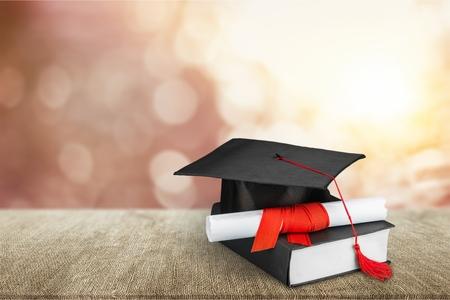 Photo pour Graduation mortarboard on  book on  background - image libre de droit