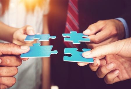 Foto de Business people holding puzzle pieces. problem solution concept - Imagen libre de derechos