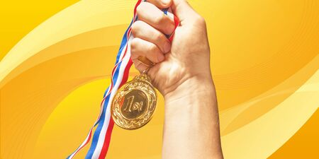 Photo pour Gold medal with ribbon in hand on - image libre de droit