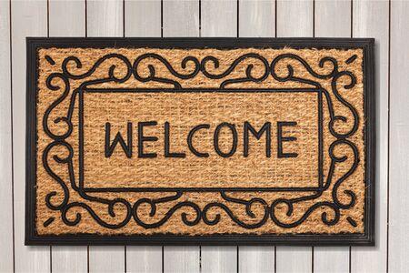 Foto de New welcome doormat on wooden floor - Imagen libre de derechos