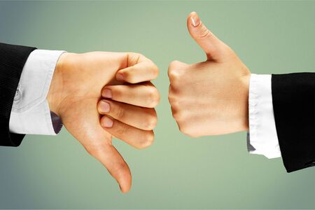 Human hands showing agree sign Versus disagree on background