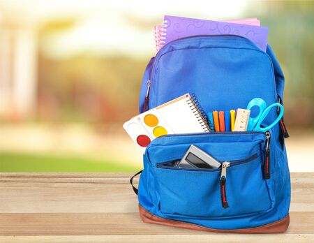 Photo pour Colorful school supplies in backpack on wooden background - image libre de droit
