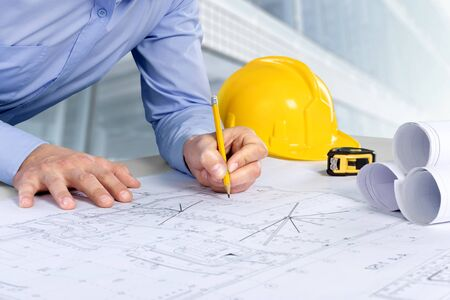 Photo pour Architect working on construction blueprint. Architects workplace - architectural project, blueprints, helmet, measuring tape, Construction concept. Engineering tools. - image libre de droit