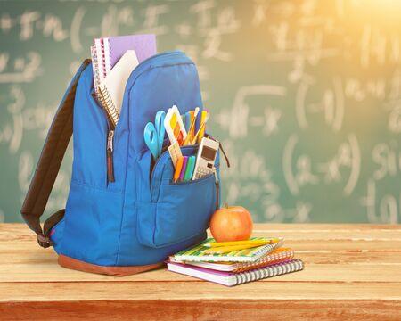 Photo pour Open blue school backpack and notebook with apple - image libre de droit