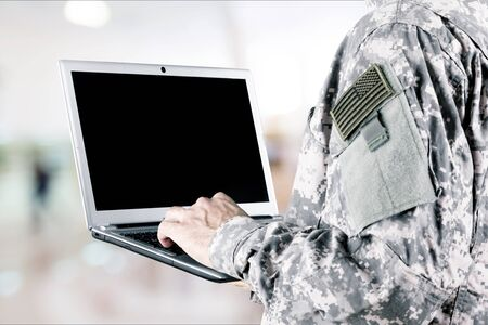 Young military man using laptop