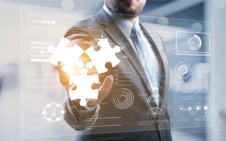 Photo pour Mergers and acquisition concept with consultant touching icons of puzzle pieces representing the merging of two companies or joint venture, partnership - image libre de droit