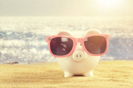 Photo for Summer piggy bank with sunglasses on the beach - Royalty Free Image