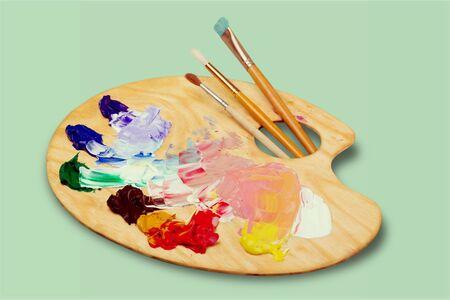Foto de Wooden art palette with blobs of paint and a brushes on white background - Imagen libre de derechos