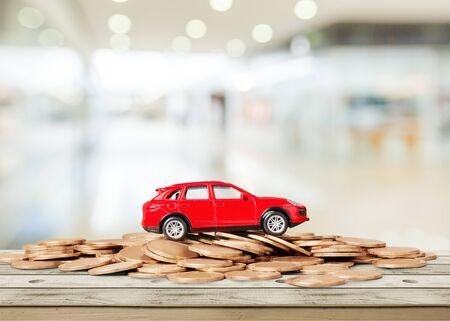 Photo pour Golden coins and toy car on  background - image libre de droit