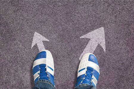 Photo pour Shoes on the asphalt road with drawn arrow - image libre de droit