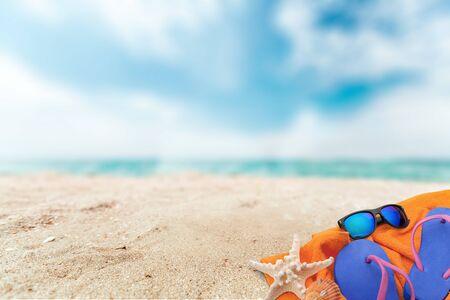 Photo pour Straw hat, bag, flip flops on beach - image libre de droit