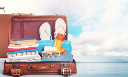 Photo pour Retro suitcase with travel objects  on sea background - image libre de droit