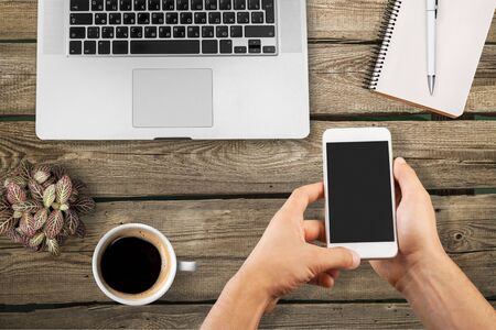 Photo pour man hands holding smartphone with blank screen for advertisement. Top view of hands, laptop keyboard, coffee, mobile on dark wooden table background, copy space - image libre de droit