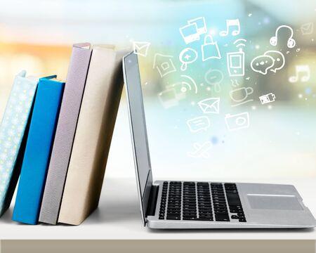 Foto de Stack of books with laptop on table - Imagen libre de derechos