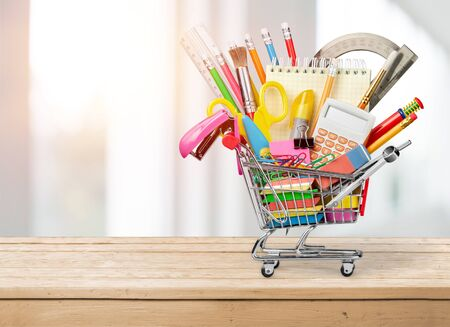 Photo for Stationery objects in mini supermarket cart on  background - Royalty Free Image