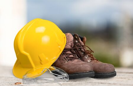 Photo pour Safety helmet with earphones and goggles on construction background - image libre de droit