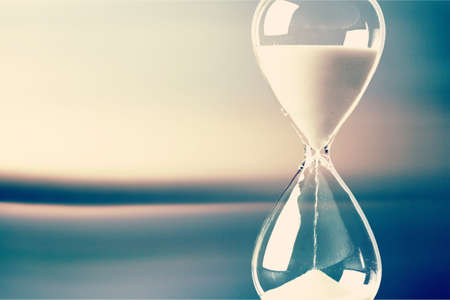 Photo pour Modern Hourglass with blurry window-view background -- sand trickling through the bulbs of a crystal sand glass. every second counts. symbol of time. countdown. - image libre de droit
