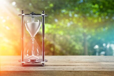 Photo pour Hourglass in the grass time during sunset. - image libre de droit