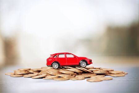 Foto de Golden coins and toy car on  background - Imagen libre de derechos