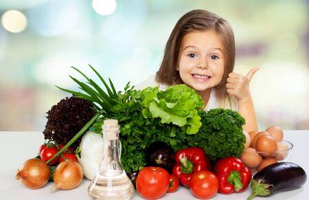 Photo pour Cute little girl with vegetables in kitchen - image libre de droit