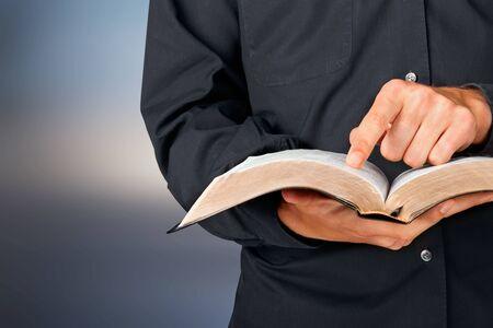 Photo pour Man reading old heavy book on background - image libre de droit