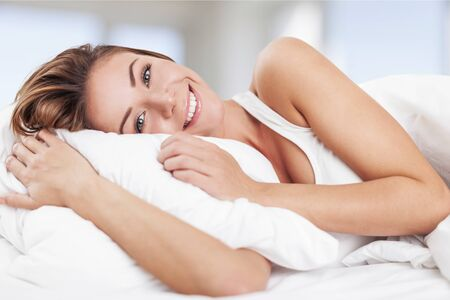Photo pour Cheerful Young Woman in Bed - image libre de droit