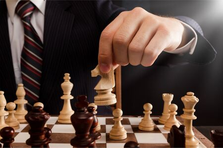 Photo pour Businessman Hand Holding a Chess Piece on a Chessboard - image libre de droit