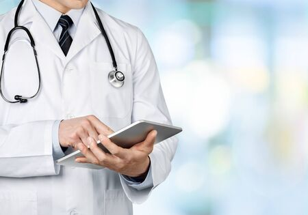 Photo pour Close-up Doctor at hospital working with tablet pc - image libre de droit