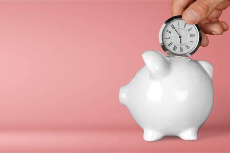 Photo pour Hand depositing clock in piggy bank - image libre de droit