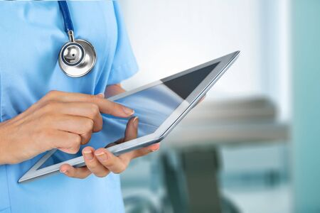 Photo pour Doctor at hospital working with tablet - image libre de droit