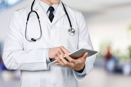 Photo pour Close-up Doctor at hospital working with tablet - image libre de droit