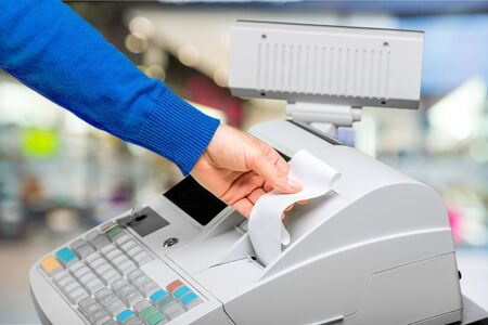 Photo pour Cash register with LCD display and worker's hand holding receipt paper over blurred supermarket interor - image libre de droit