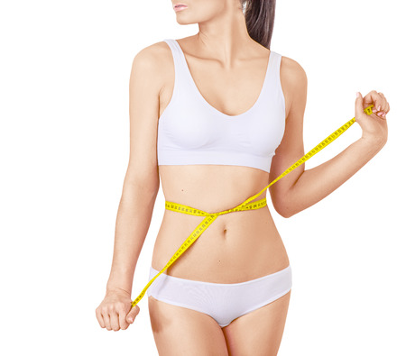 Slim woman in white underwear and measure around her body on isolated background. Healthcare, diet, weight loss and body care concept. Without face