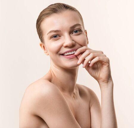 Foto de Studio portrait of young, smiling woman. Healthcare, skincare concept on the peach color background - Imagen libre de derechos