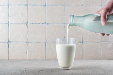 Photo pour Pouring milk on the kitchen background with ceramic tiles - image libre de droit