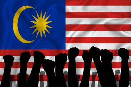 Photo pour Silhouette of raised arms and clenched fists on the background of the flag of Malaysia. The concept of power, power, conflict. With place for your text. - image libre de droit