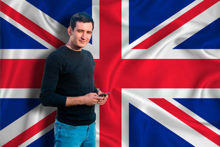 Photo pour Great Britain flag on the background of the texture. The young man smiles and holds a smartphone in his hand. The concept of design solutions. - image libre de droit