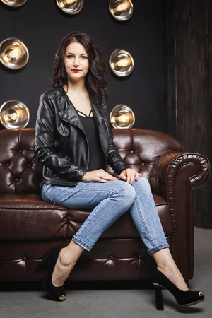 Woman with long brunette hair in black coat and blue jeans sitting on brown leather couch in the studio